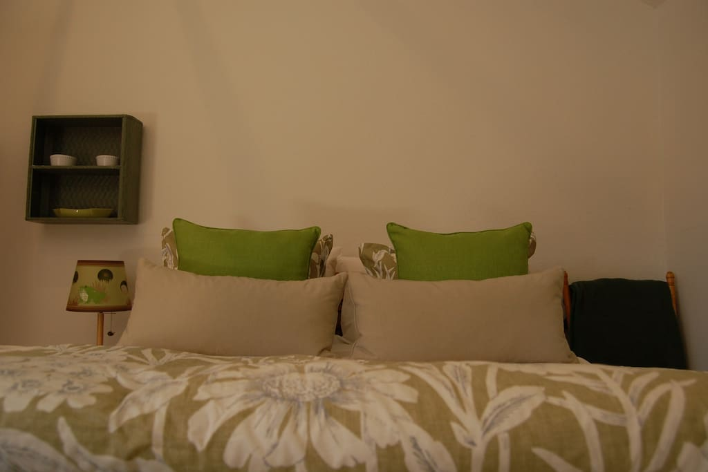 Queen bed has luxury linens.