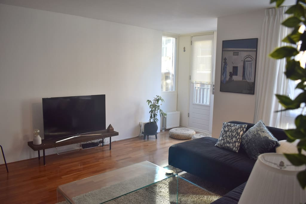 """Living room with large screen smart TV  """"Ambreen's place is perfect for a stay in Amsterdam. Situated in a quiet street in a great local neighborhood, close to the center. Clean, comfortable, with everything you need at hand. Would definitely recommend."""" - Michelle. *****"""