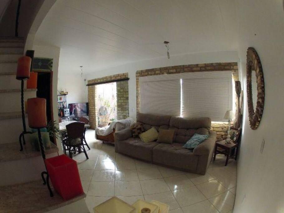 Sala de estar, com TV 42 polegadas, bem iluminada e arejada.