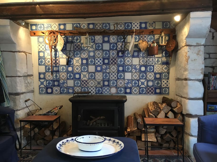The woodturning stove in a huge inglenook with local blue and white tiles.