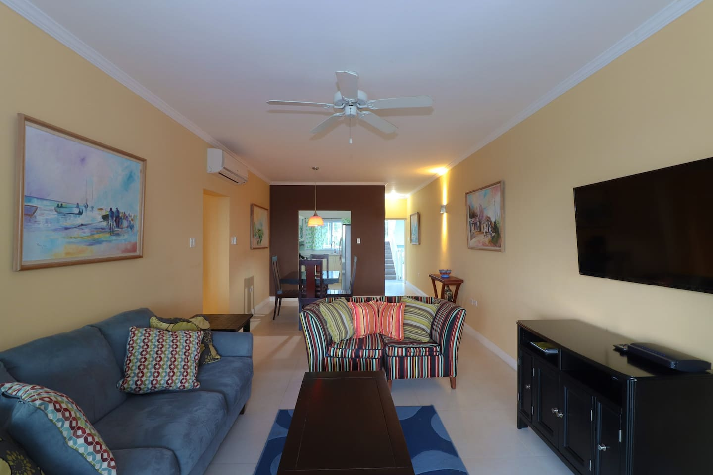 Living Area with dining table and kitchen entrance. Equipped with WiFi and HD tv, A/C and ceiling fan