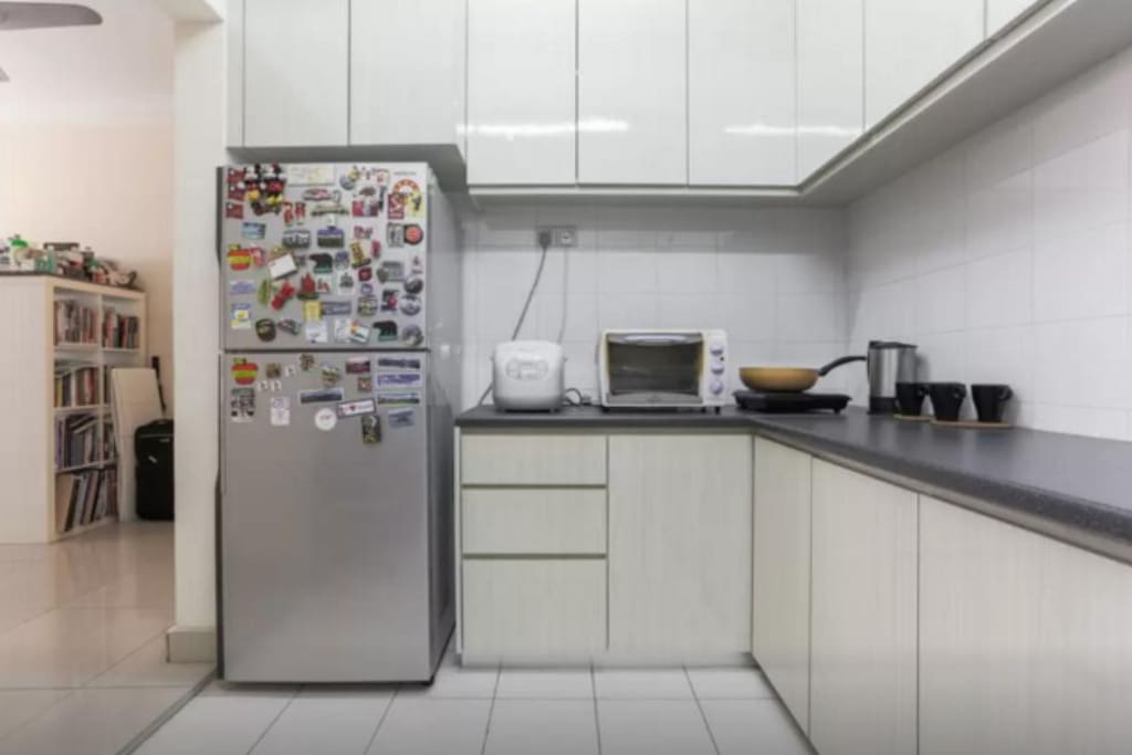 Kitchen with fridge, rice cooker, oven, induction cooker and frying pan.