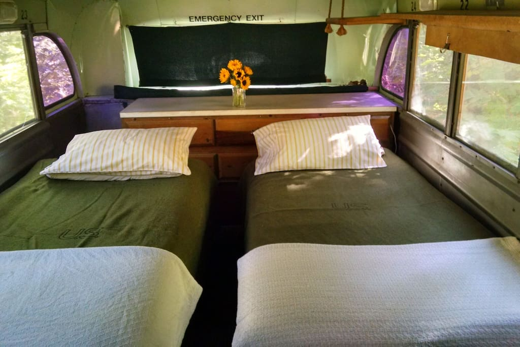 Two comfortable twin beds in rear of the bus with real mattresses, feather comforters, soft pillows and wool blankets on top