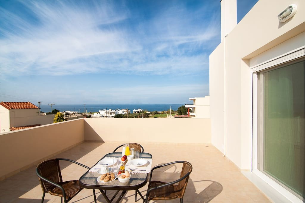 Shaded sitting/dining area upstairs withnice views to the sea!