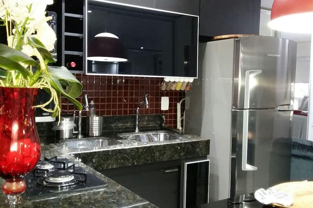 Agradável cozinha equipada com geladeira, microondas, cooktop, purificador de água com opção de água gelada e natural, duas cubas e utensílios de cozinha