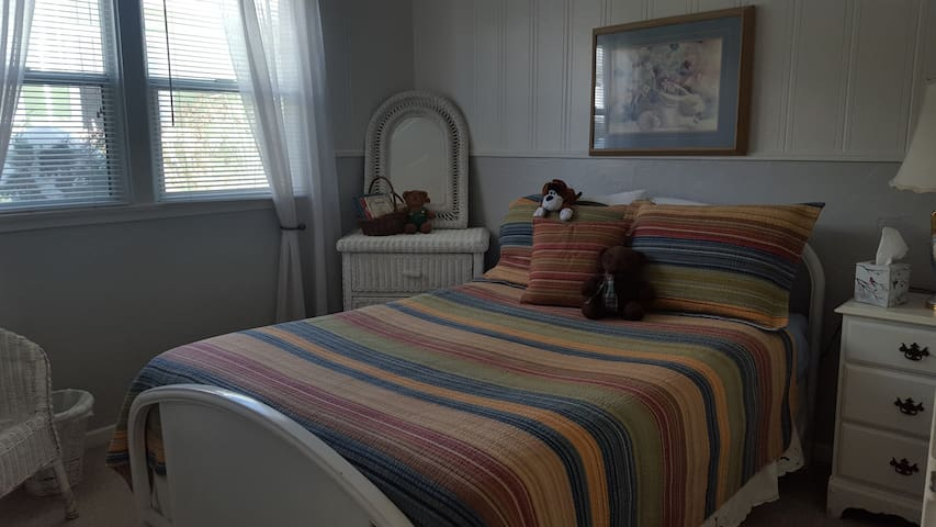 Back Bedroom  Furnished in white wicker, with a double bed, rocking chair, & dresser the large windows provide a spacious open feeling. The linens and comforter add luxury to this bedroom and insure a great night's sleep.