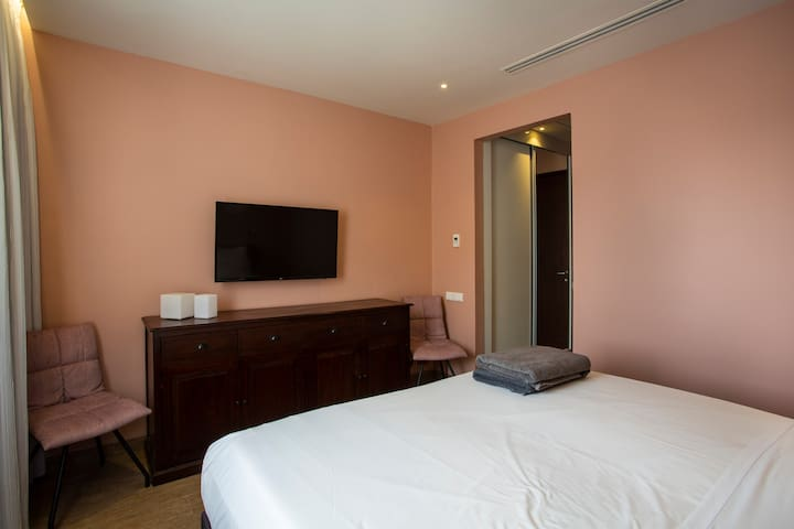 Bedroom 2 with TV and adjoining bathroom
