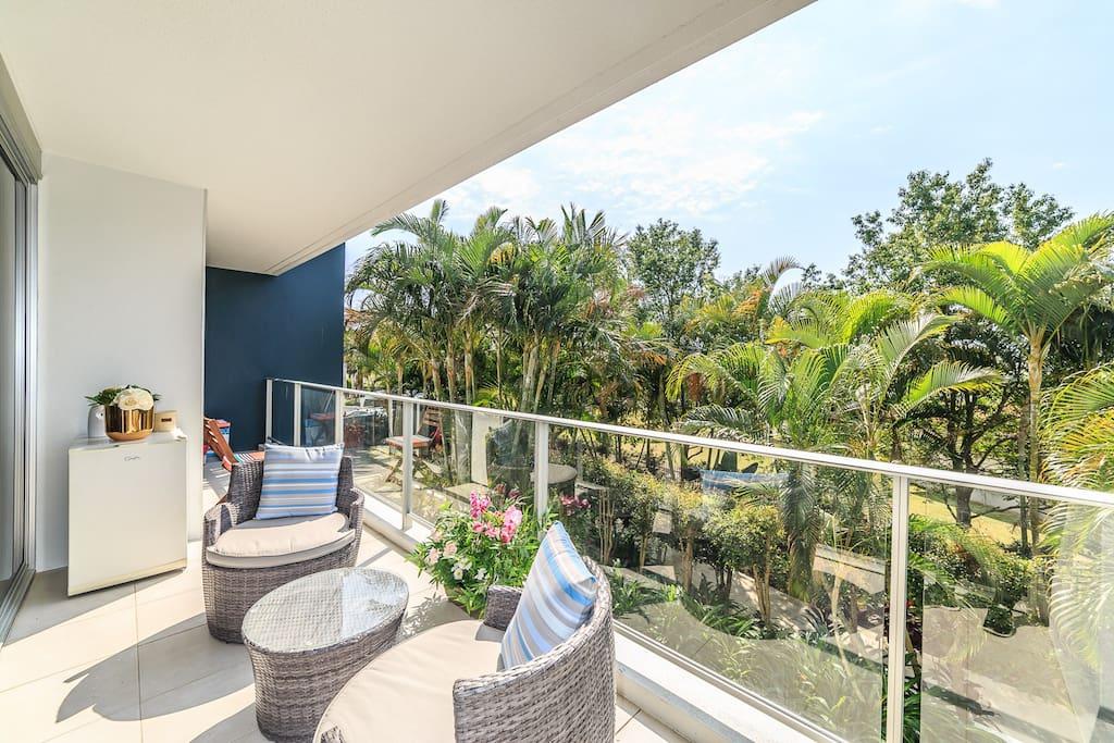 Sun filled balcony overlooking lush gardens