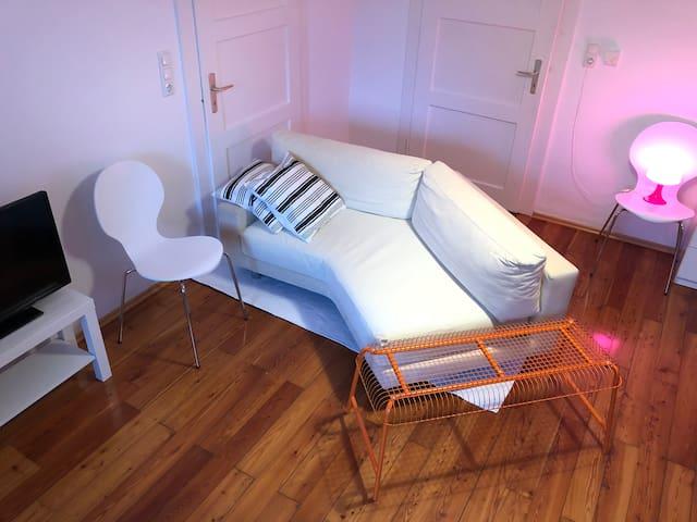 Zimmer 2 mit TV, Sofa und 2 individuellen Betten. Wunderschöner alter Holzboden