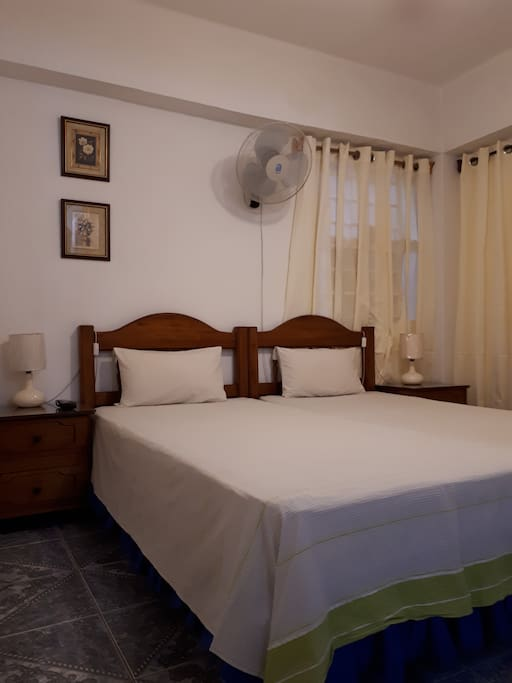 The bedroom (equipped with two single beds that can be placed together for couples, or separated). The room has AC!