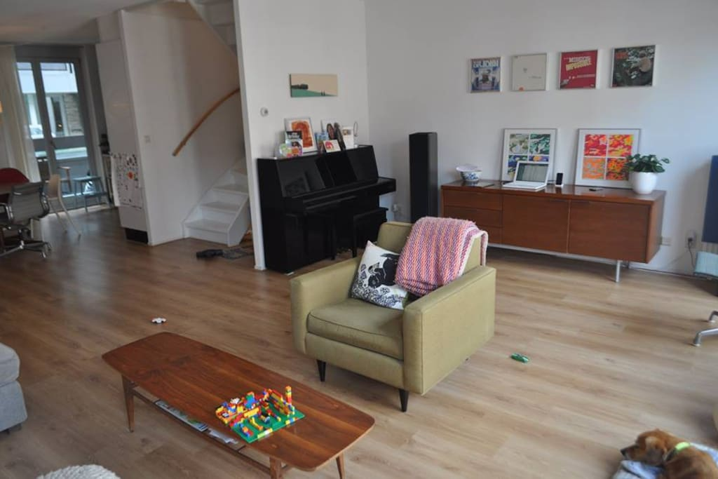 Spacious living room with comfortable couch, piano, stereo and television.