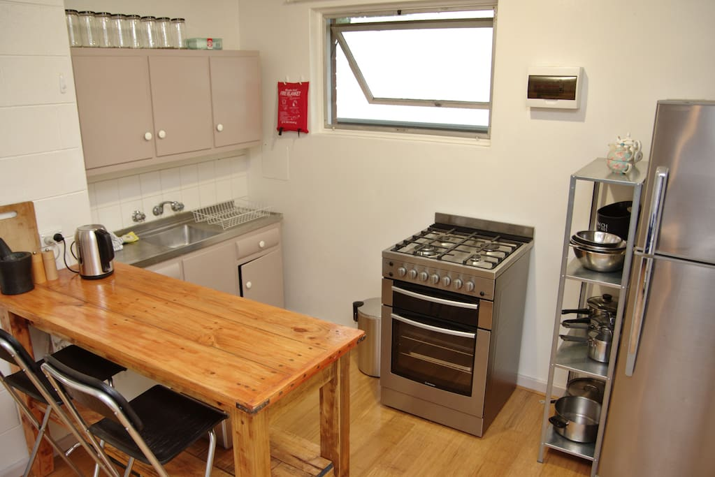 Kitchen with gas stove, fully stocked with equipment.