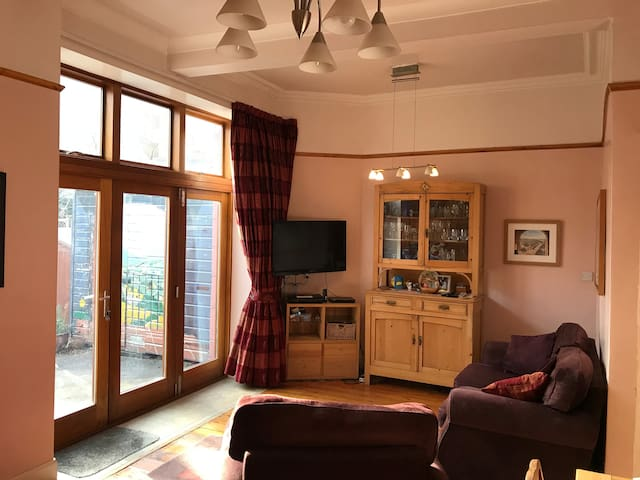 The living/dining room has a 2 seat sofa along with an arm chair, TV, DVD player and wonderful view out into the back garden.