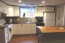 Kitchen, with many amenities. Soft close cabinet doors, pull down faucet, dishwasher, oven, coffee makers, electric kettle, toaster, fridge, waffle iron, electric griddle, microwave, electric slow cooker & large window looking into private backyard.