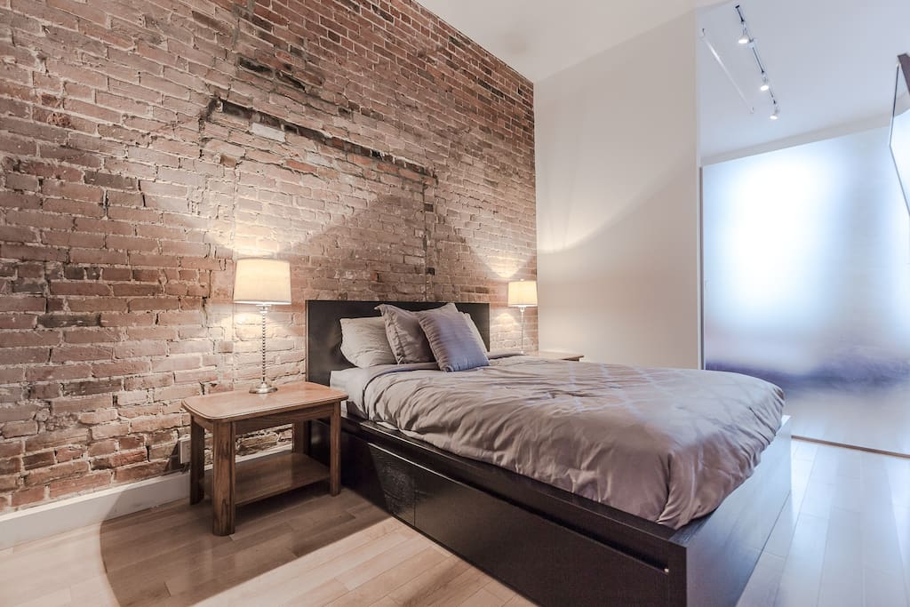 Stunning queen-size bedroom with brick wall