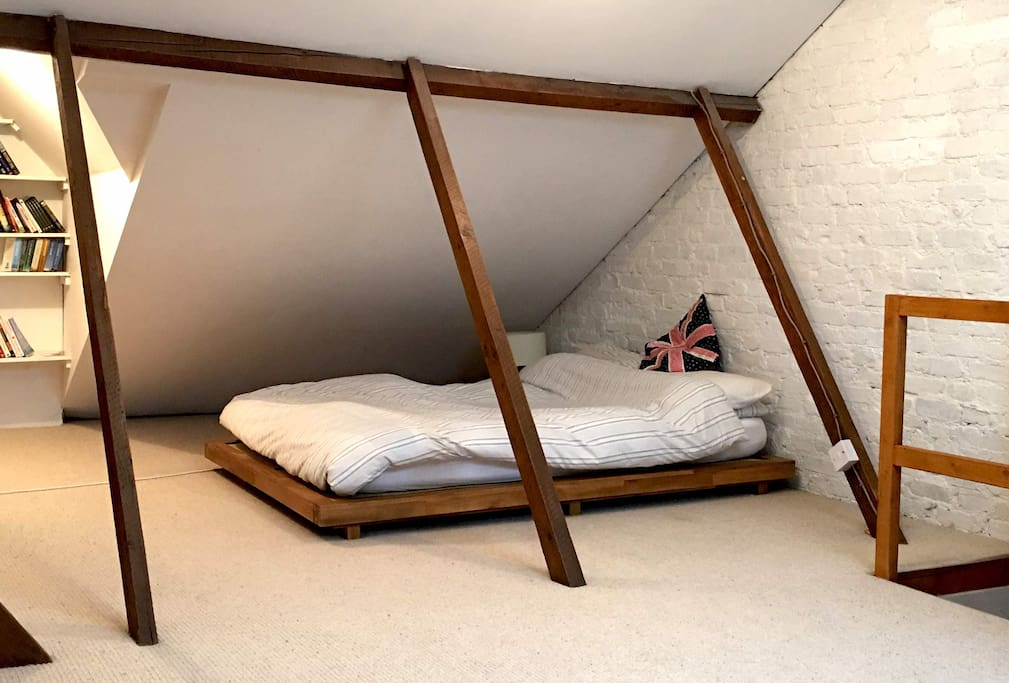 The main Bedroom is a beautiful loft space with lots of natural wooden features