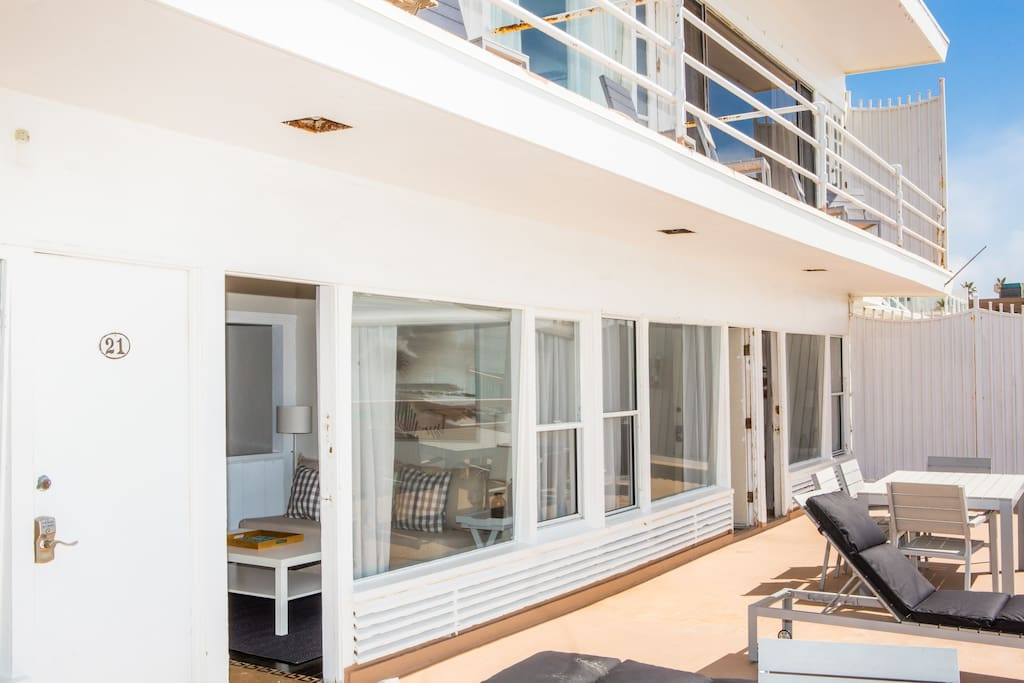 Studio connects to a semi private deck with lounge chairs and a patio table