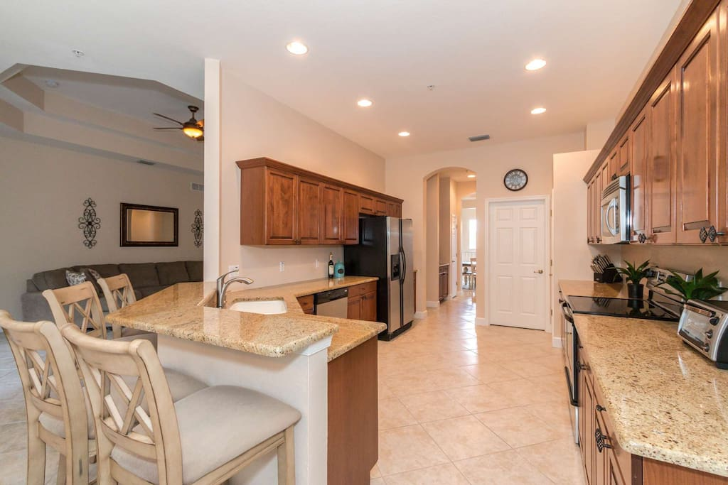 Elegant, full-sized kitchen, complete with granite counter tops, stainless appliances, and abundant cupboard space.