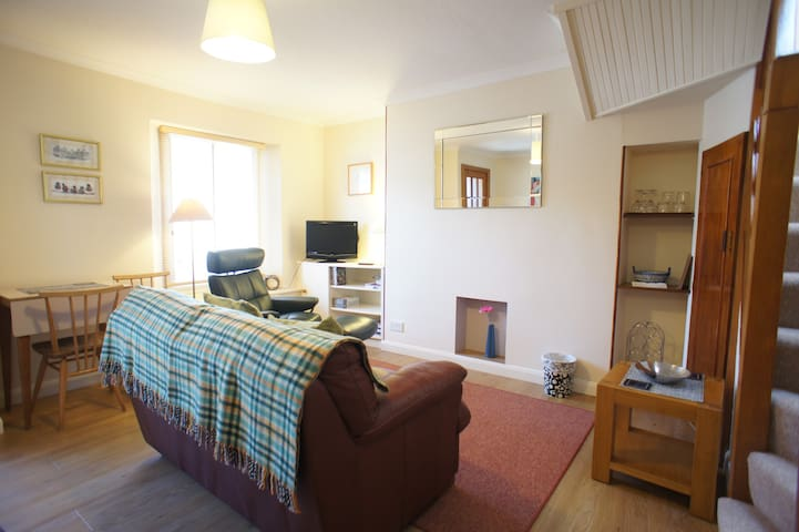 Bright living room with dining area and flat screen television and free WI-FI internet