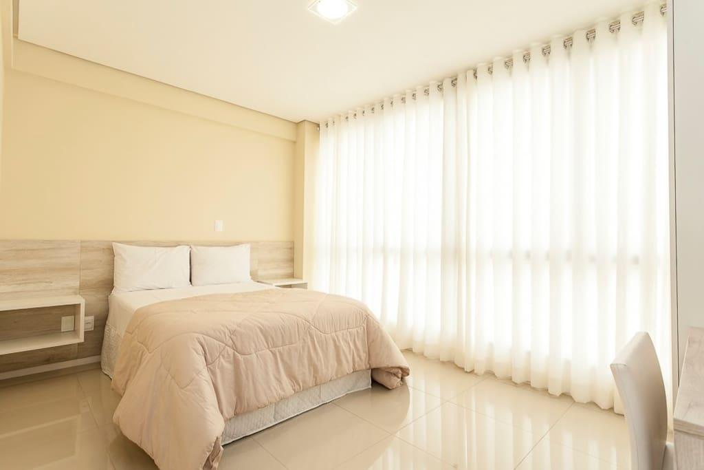 Quarto com cama de casal com cabeceira, ar-condicionado, guarda roupa, mesa de trabalho.