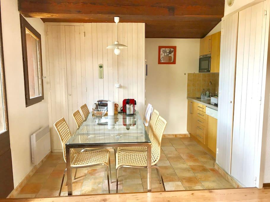 La grande table de la salle à manger et la cuisine à droite