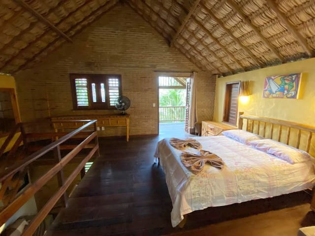 Quarto grande e iluminado com uma cama de casal, ventilador, armários banheiro e acesso à varanda do segundo andar.
