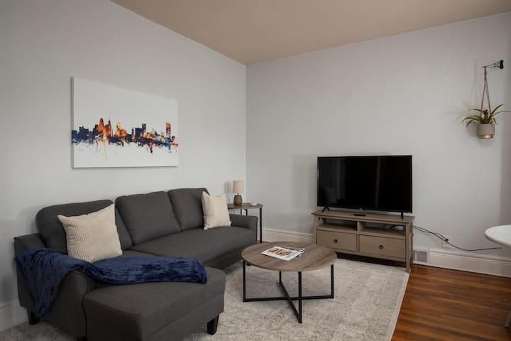 Spacious living room with comfortable sleeper sofa and smart TV.