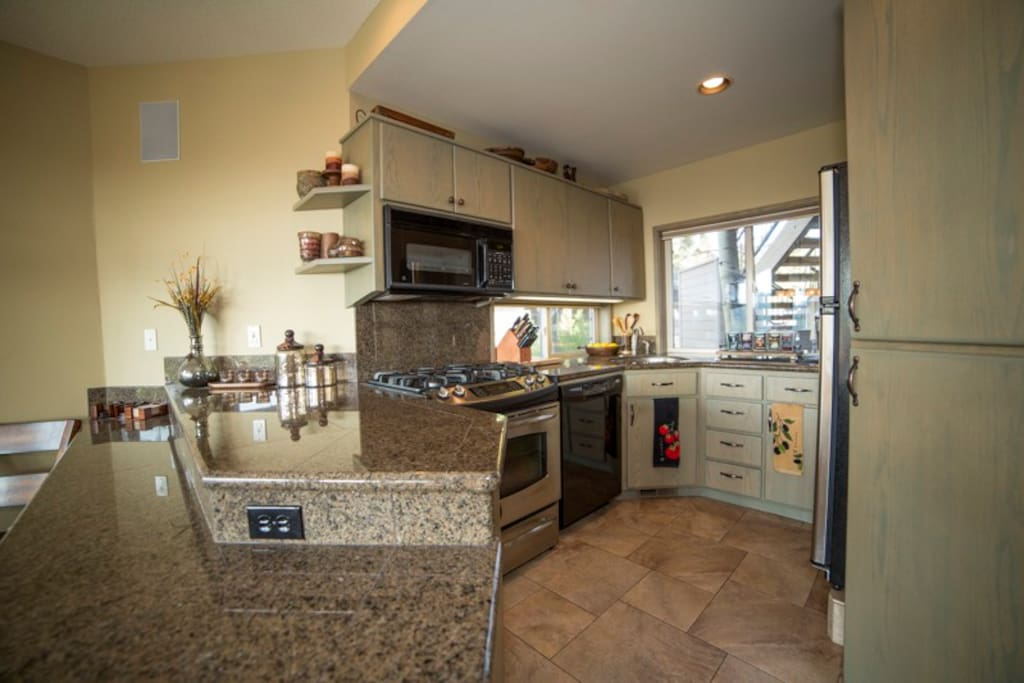 A fully equipped kitchen with granite tiled counter tops and stainless steel appliances and a four burner gas range and breakfast bar for two.