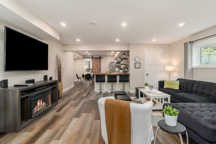 Large living room with ample seating and a cozy electric fireplace.   Large 65in TV complete with Bell Fibe TV, Netflix and surround sound.