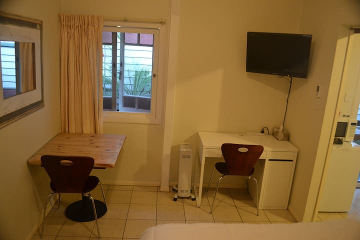 TV, table and chairs plus a desk, WiFi access , heater and ceiling fan