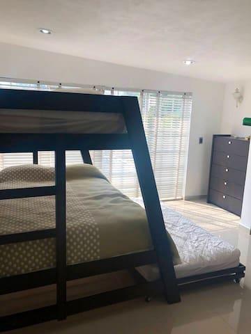 Recámara con 1 cama matrimonial y 2 camas  individuales, closet, aire acondicionado, baño privado y vista a la alberca