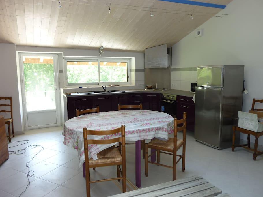 le coin cuisine, entièrement équipé, donnant sur une terrasse avec accès sur terrain