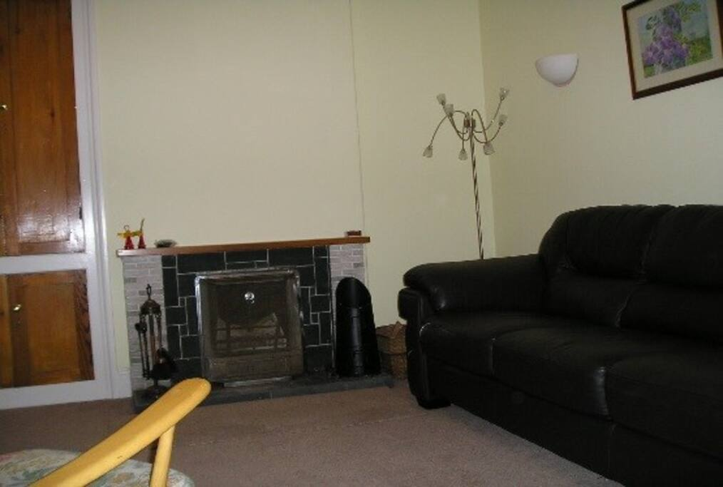 A cosy lounge with large sofa, two armchairs and open fire.