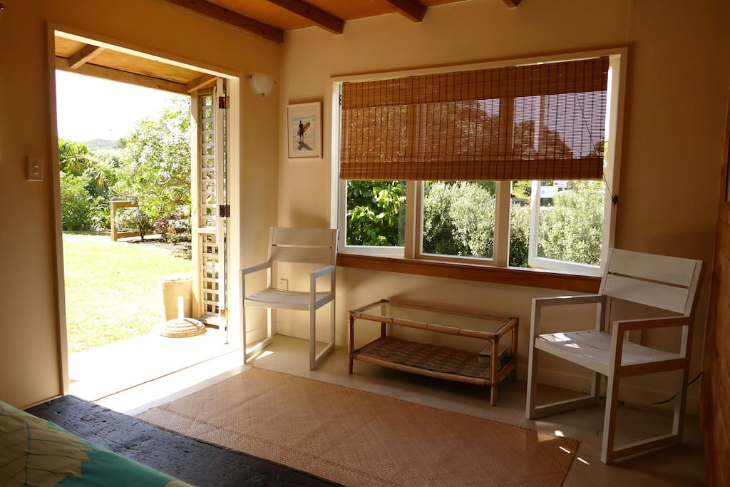 The cabin bedroom opens out onto sunny  lawn.