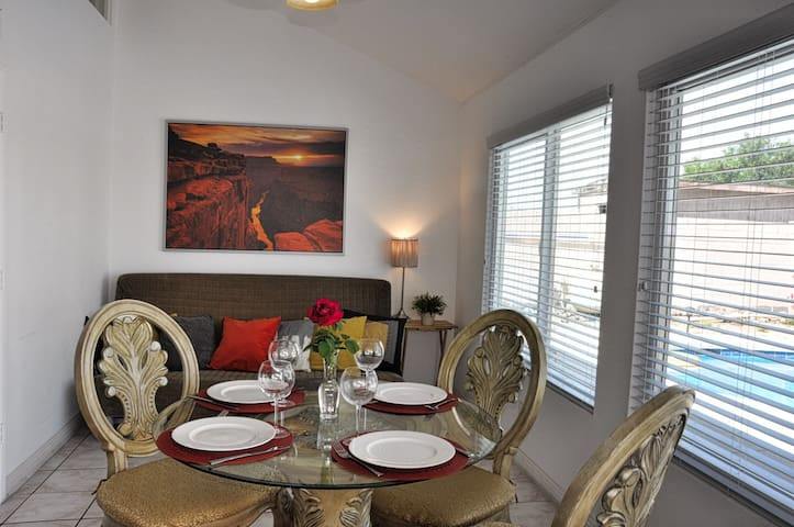Spacious dining area, table with 4 chairs. Back - queen size sofa.