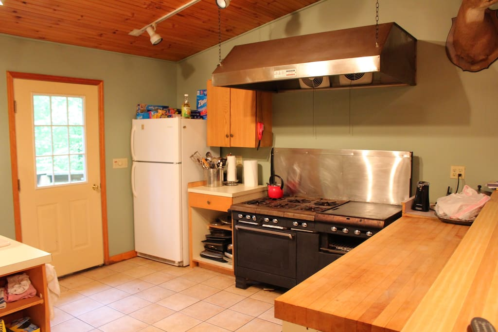 Industrial stove with butcher block counter top, underneath breakfast bar.  Outdoor grill on the porch outside the kitchen.   Perfect for big meals.  3 full size refrigerators for stocking food and drinks.