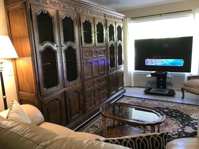 Large cabinet, 65 inch television, gold leather sofa and love seat provide comfortable living room area for guests.