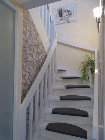 Treppenaufgang zum Zimmer mit mediterranem Charme über eine Galerie.