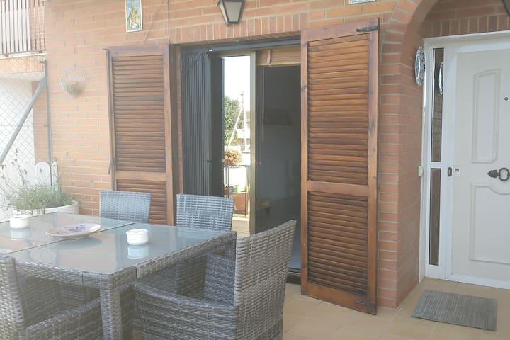 Aquí puedes ver el porche de casa, con mesas y sillas de jardín donde podrás hacer vida exterior en un ambiente exclusivo para ti y tu familia o amigos.