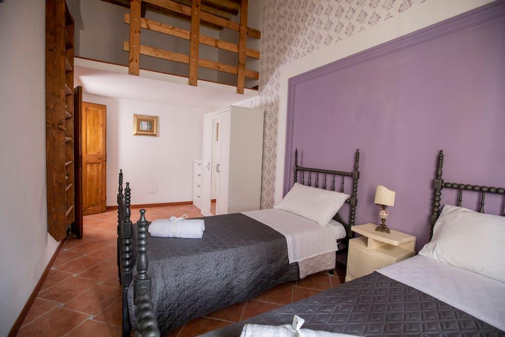 Camera Assisi con due letti singoli in materasso Memory dotata di aria condizionata, tv, armadio, cassettiera, un soppalco utilizzabile e decorata con tinta decorativa Damasco.