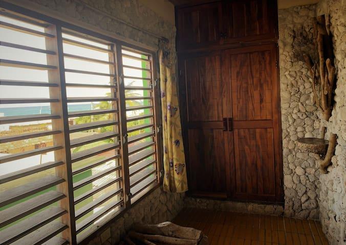 Amplios ventanales y trabajos de carpinteria rustica en el dormitorio de Coral room!