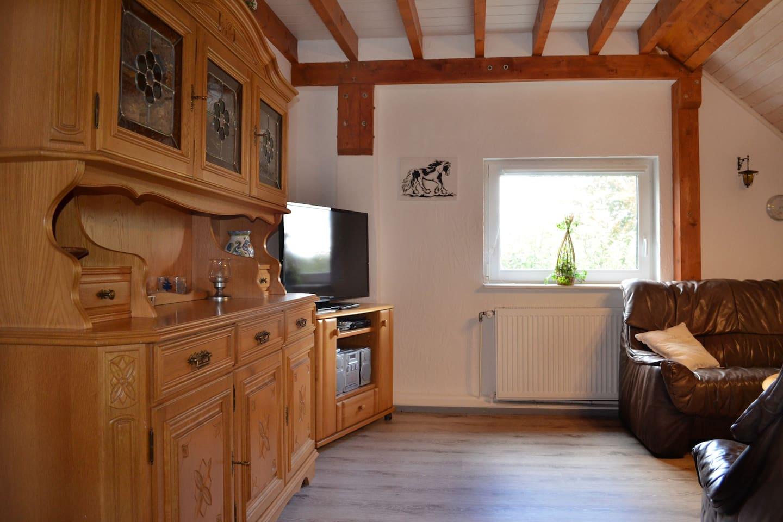 Wohnzimmer in offener Bauweise mit angrenzender Wohnküche