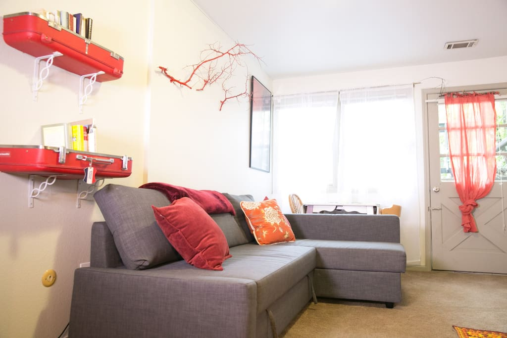 Brightly decorated fun living room area. This couch folds out into a second bed to accommodate an extra guest.