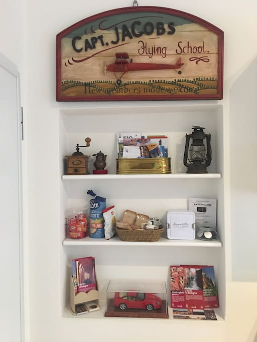 """Entrance with bulletin board. In the central shelf, the """"Welkome Kit"""", with bread, nutella, jam, honey, Nespresso coffee, tea"""
