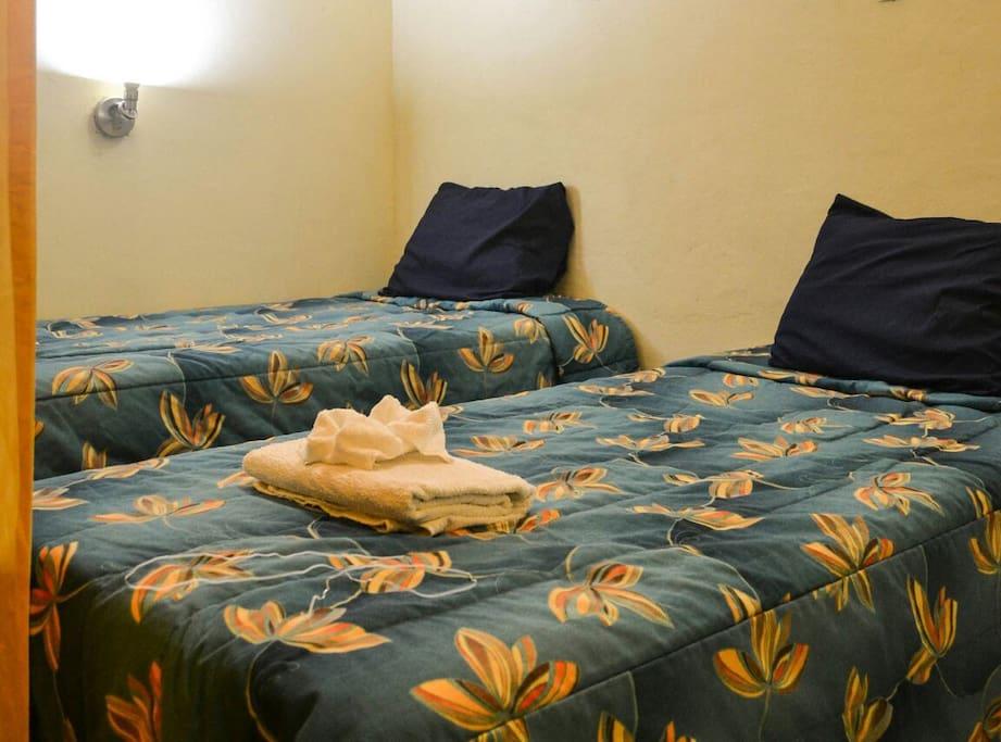 Cubiculo para 3 personas una cama matrimonial y una individual. Con baños compartidos. Y puerta corrediza