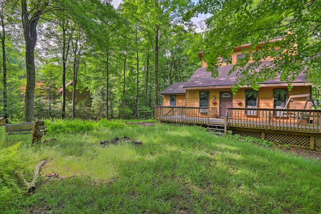 Lush greenery surrounds this 3-bedroom, 2-bath lodge on 1 wooded acre.