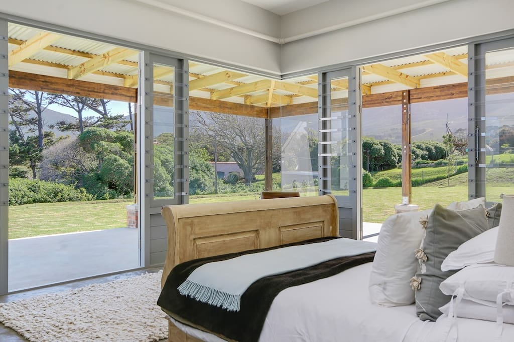 main bedroom with mountain views, doors onto the garden, dam and swimming pool, with a large en suite bathroom