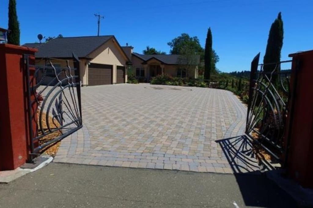 Through the gates, a large driveway leads to a 2 car garage and parking for 6 - 8 additional cars.