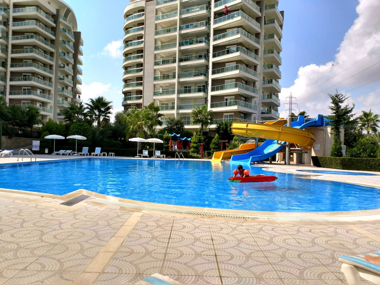 Large pool area with a shallow pool for children, two different waterslides and a playground on the side.