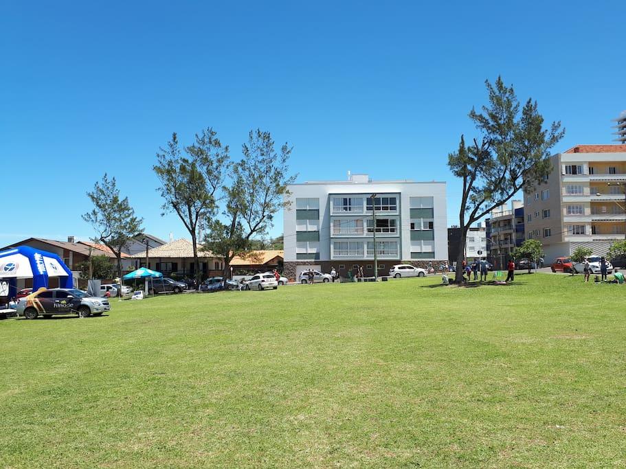 Praça em frente ao prédio toda gramada